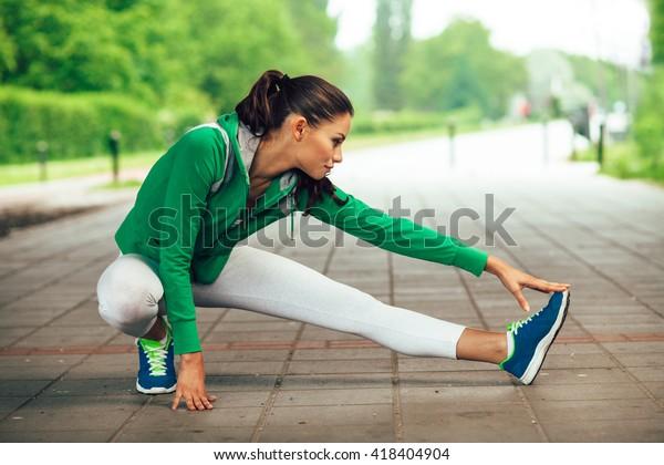 Junge Fitnesslutnerin, die sich vor dem Laufen die Beine streckt