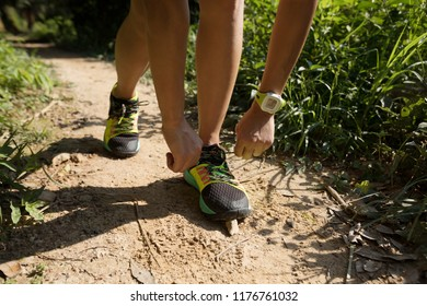 Young fitness woman runner tying shoelace on forest trail