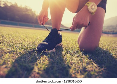 Young fitness woman  runner tying shoelace on stadium grass