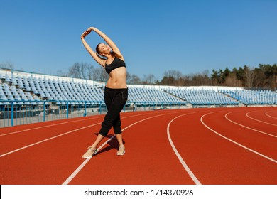 young fitness woman runner warm up before running on track. Morning exercises at summer Stretching. Healthy lifestyle