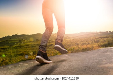 young fitness woman  running on road at sunset in nature