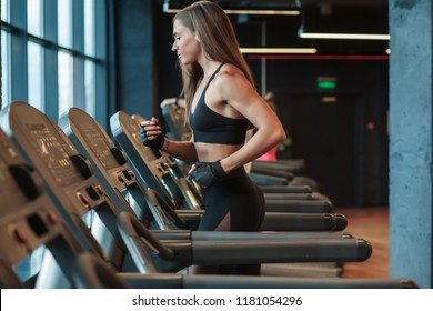 young fitness woman running on treadmill in gym