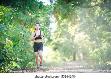 Young fitness woman running on a rural road. Sport woman running,Healthy lifestyle concept.