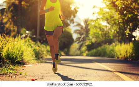 Young fitness woman running on morning tropical forest trail