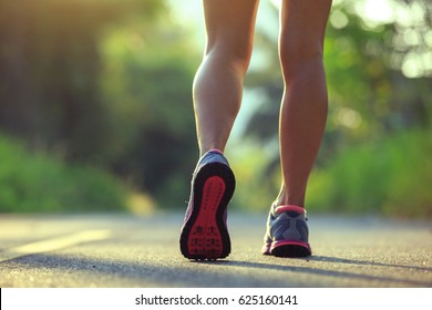 Young fitness woman running on morning tropical forest trail  - Shutterstock ID 625160141