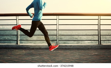young fitness woman running at seaside