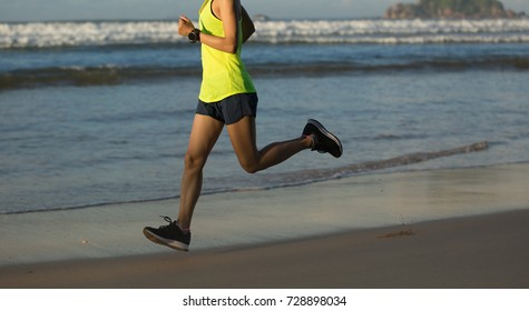 Young fitness woman running at the sunrise seaside
