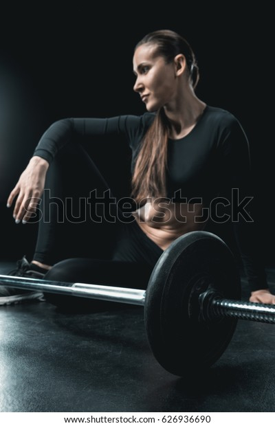 young fitness woman sitting at barbell and resting isolated on black.