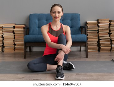 Young fitness woman sitting on floor at home