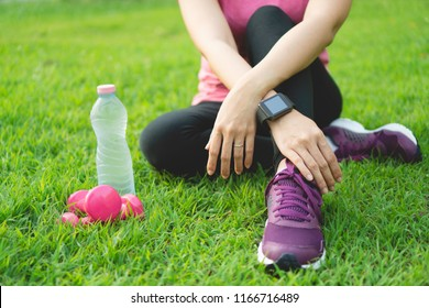Young fitness woman sitting on lawn for rest after workout training with dumbbells and water bottle in park. Fitness female in sportswear and smart watch tracker exercise outdoor. Healthy lifestyle.