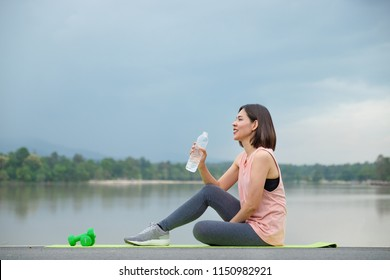 Young Fitness woman smiling and holding drinking water after yoga in the park. Healthy Lifestyle concept.