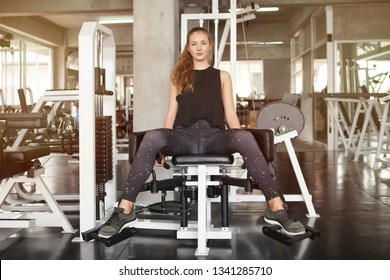 young fitness woman in sportswear exercises open legs muscles with push machine in gym . sport girl workout healthy lifestyle.training morning light