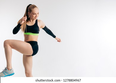 a young fitness woman in sportswear raising her knees and doing exercises. close up photo. copy space. hobby, lifestyle, sporty life