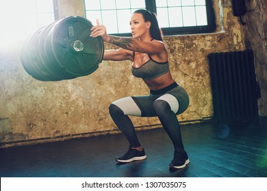 Young fitness woman standing with heavy weight barrel. Soft warm sunlight light.