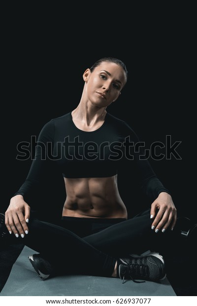 young fitness woman stretching neck while sitting on mat isolated on black.