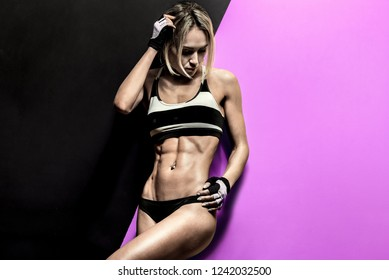 young fitness woman in swimsuit on black and mauve background, horizontal photo