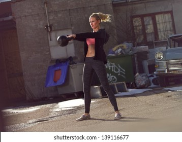 Young fitness woman swinging the kettlebell during crossfit training
