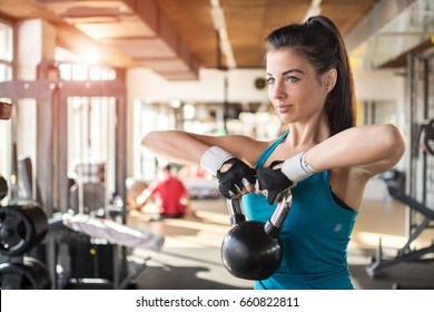 Young fitness woman swinging the kettlebell during crossfit training. Athletic girl doing workout in a fitness center.