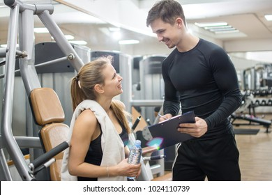 Young fitness woman talking with her personal trainer in the gym.