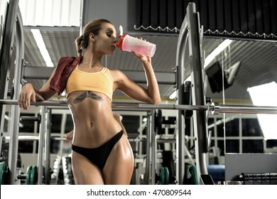 young fitness woman tired in gym drink sportive nutrition , Amino Acid or bcaa of shaker , horizontal photo