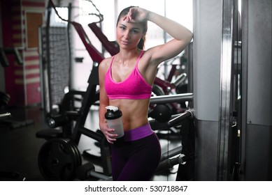 young fitness woman tired in gym with sportive nutrition , Amino Acid or bcaa of shaker