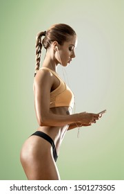 young fitness woman tired and listen music with headset on green background, vertical photo