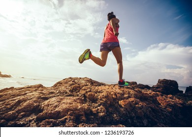 Young fitness woman trail runner running to rocky mountain top on seaside