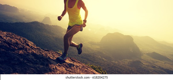 Young fitness woman trail runner running up at mountain top cliff edge