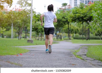 young fitness woman walking in the park outdoor, female runner running on the road outside, asian athlete jogging and exercise on footpath in sunlight morning. Sport, healthy and wellness concepts