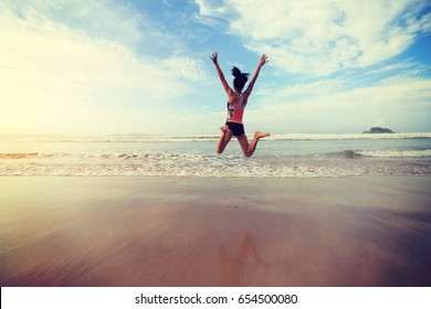 young fitness woman wear swimsuit jumping on beach
