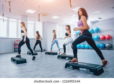 Young fitness women using step platform at the gym. Crossfit training. Fitness concept.
