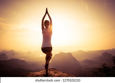 young fitness yoga woman meditating on sunrise mountain peak