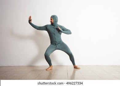 Young and fitted bearded athlete male wearing his winter snowboardint baselayer thermal suite and having fun acting like a ninja