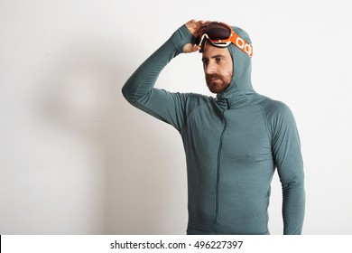 Young fitted bearded male athlete in baselayer thermal suite removes his snowboarding googles with one hand, isolated on white background