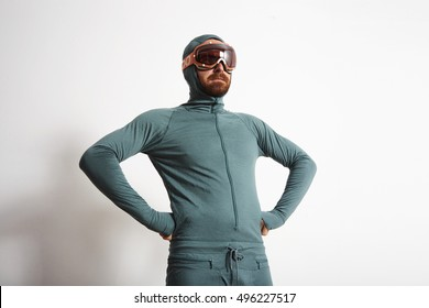 Young fitted bearded male athlete in baselayer thermal suite wears snowboarding googles, proudly stands in front of white wall