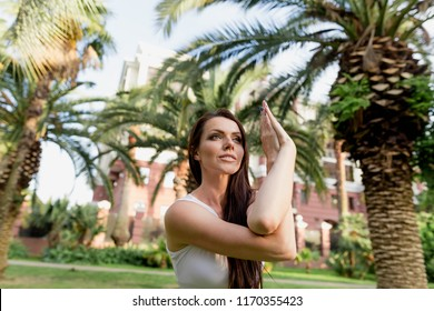 Young fittness instructor female in white active wear has pilates training in morning at park. Half size portrait at palm trees background.
