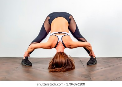 a young flexible girl does yoga. you stretch your legs. yoga pose standing, deep tilt. The girl does a sports exercise, leans forward against the background of a light wall.