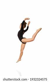 Young flexible slim gymnast girl in gracefull jump