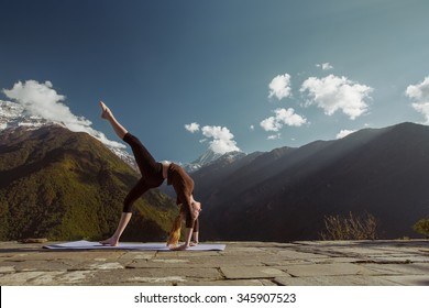 Young flexible woman doing sport yoga exercise brig asana in beautiful mountains landscape on the sunrise