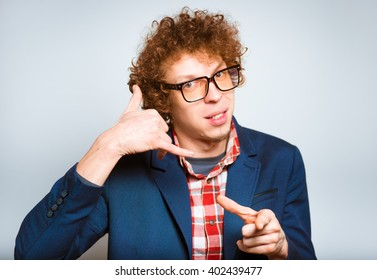 young flirtatious man making call me gesture over white background