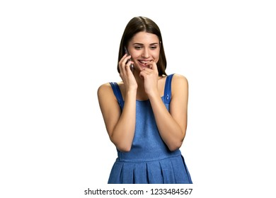 Young flirty woman talking on phone. Joyful girl talking on cell phone while touching her lips, isolated on white background.