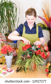 Young florist cutting flowers and working on an arrangement