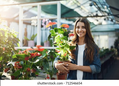 Young florist or gardener holding an anthurium flower for sale looking at camera smiling