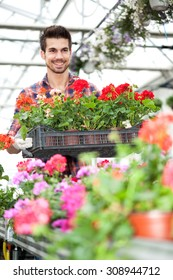 young florist man working with flowers at a greenhouse
