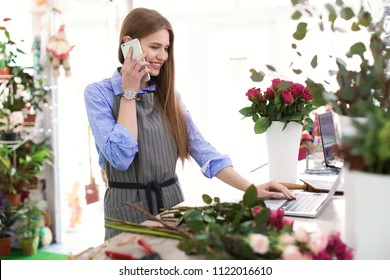 Young florist working with laptop and talking on mobile phone in flower shop