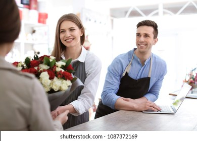 Young florists with customer in flower shop