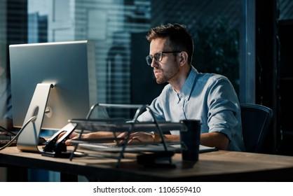 Young focused man doing overtime job watching computer at desktop in dark office.