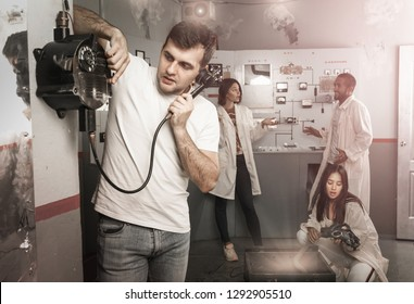 Young focused man using old telephone while visiting with friends quest room in view as closed nuclear bunker