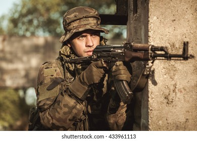 Young focused soldier in uniform pointing his rifle