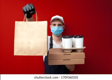 young food delivery man in a protective mask and gloves holds boxes of food and gives the client, quick delivery service during the epidemic of coronavirus